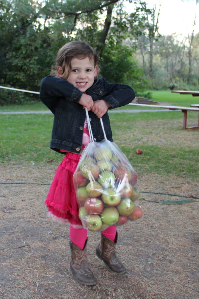 Madiana showing how strong he is by holding up the bag of apples