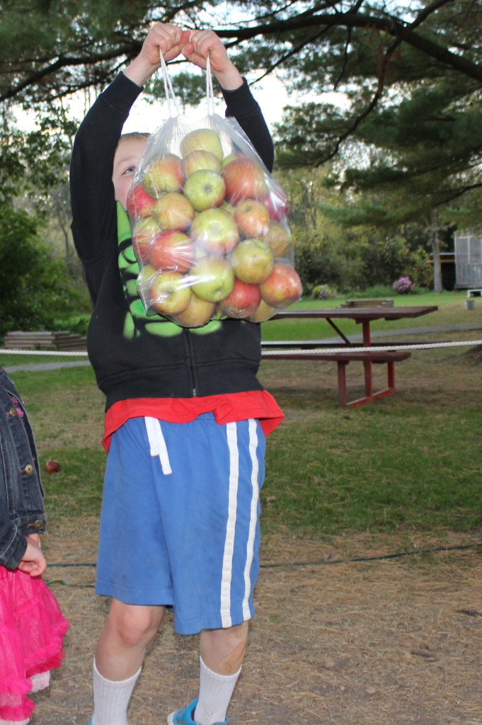 Brecken showing how strong he is by holding up the bag of apples